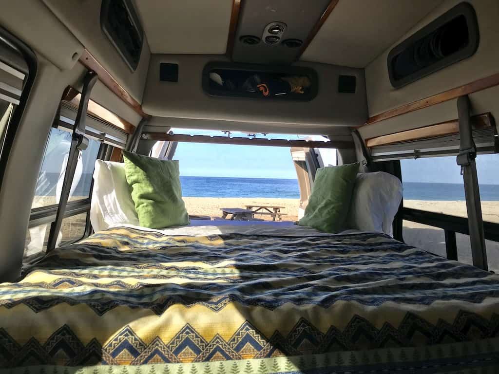 the inside of my van with a bed overlooking the beach