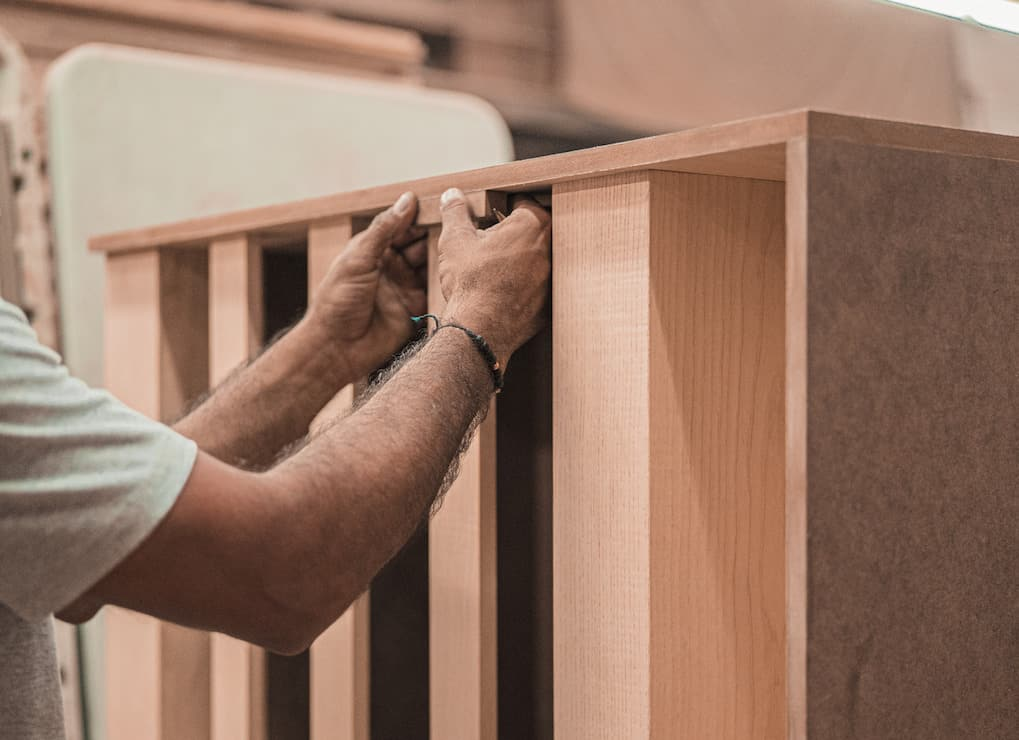 a person assembling a cabinet