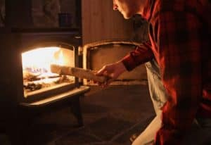man putting firewood in a wood stove