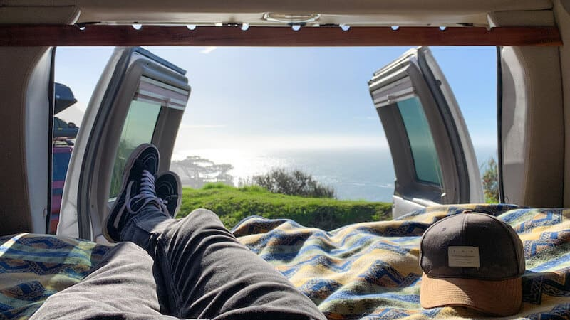 laying in a bed in a van with a view of the ocean at Big Sur, CA
