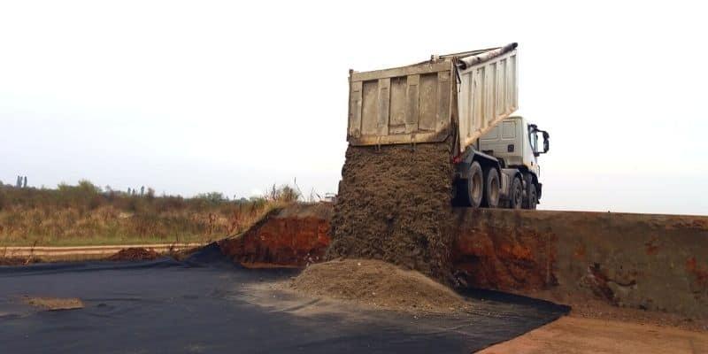 a truck dumping dirt on a property